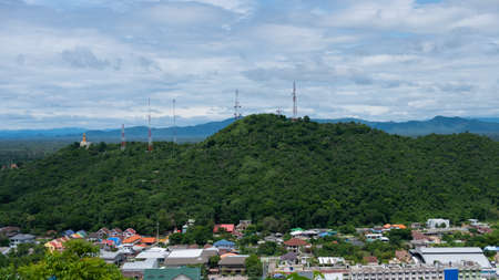 Mountain view with signal towers of various communications. Which is surrounded by residential houses of the city people in Thailand
