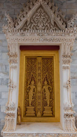The gates of the temple church are carved with beautiful Thai patterns on Buddhism.