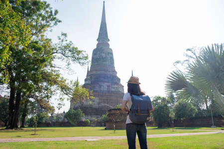 Asian woman tourists carrying a backpack and wearing a hat Visit Wat Yai Chaimongkol, the historical archaeological site of Phra Nakhon, Ayutthaya.