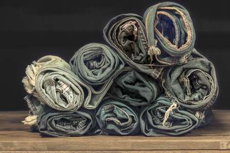 roll blue denim jeans arranged in stack.On oak wood texture background,.Ripped jeans of a stack Hipster fashion copy space for text