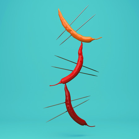 Creative Concept : Red peppers impaled floating on turquoise background. used for graphic design and website. minimal food idea concept.