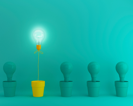 Outstanding yellow light bulbs with glowing in flowerpot one different idea from light bulbs the others on green pastel background, Minimal concept idea.