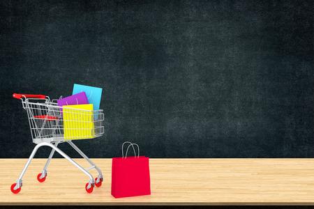 블랙 보드 배경 가진 나무 테이블에 트롤리에 다채로운 종이 쇼핑 가방. 행동 온라인 쇼핑 중독에 대한 아이디어. 아트 작업 디자인을위한 공간을 복사하거나 텍스트 메시지를 추가합니다. 스톡 콘텐츠 - 90651175