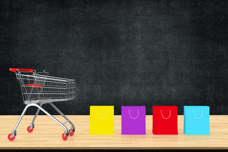 Colorful paper shopping bags with trolley on wood table with black board backdrop.  Ideas about online shopping, E-commerce online business. copy space for art work design or add text message.