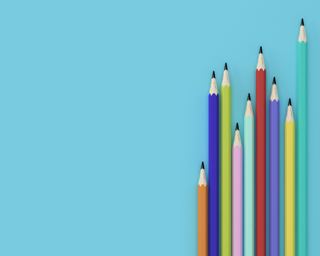 Crayons, colored pencil set loosely arranged on blue paper background. minimal creative concept.
