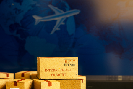 Small paper boxes on notebook with a plane flies behind. An ideas about transportation, international freight, global shipping, overseas trade, regional, or local forwarding.