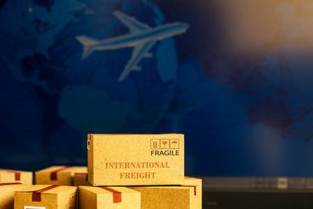 Kleine papieren dozen op notebook met een vliegtuig vliegt erachter. Een idee over transport, internationale vracht, wereldwijde verzending, overzeese handel, regionale of lokale expeditie.