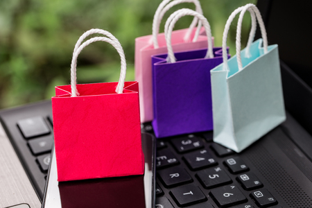 Colorful paper shopping bags with mobile phone on a laptop keyboard. Concept about online shopping that customers can buy everything from home or office. Via the tool electronics.
