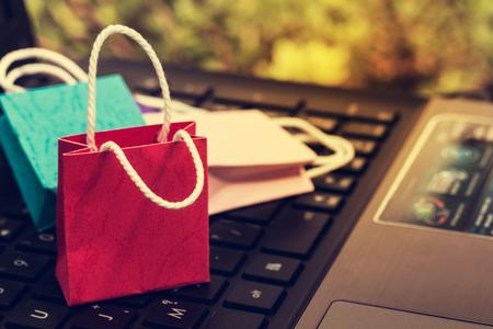 Três sacos de compras de papel colorido no teclado do notebook. Conceito de negócios de compras on-line. O comércio eletrônico ou serviços na internet é uma transação de compra ou venda de mercadorias por meio de sistema eletrônico