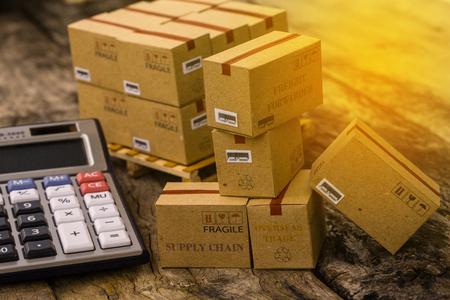 골 판지 상자 제품의 더미 나무 팔레트 계산기와 함께 더미. 투자자가 직접 보유한 자산 포트폴리오를 모으기위한 아이디어. 예상 수익은 주어진 수준