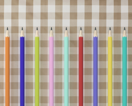 Top view of many colorful Pencils pencils on fabric tartan plaid pattern background. minimal idea concept. flat lay. concept for education. Stock Photo