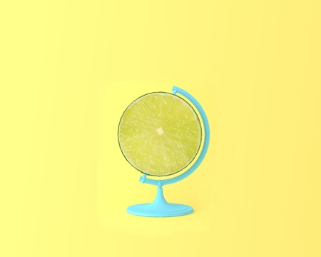 Globe sphere orb Lemon, lime slice on pastel yellow background. minimal idea food and fruit concept. Idea creative to produce work within an advertising marketing communications. Business concepts