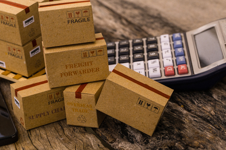 Cardboard boxes packaging the products and calculator on wood table. Concept of Increasing product rates the expansion of export business to plan marketing or finance go future.  Archivio Fotografico