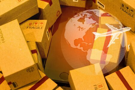 Black smartphone with World map on pile of cardboard boxes. concept of International freight or shipping service for online shopping or e-commerce concept. freight forwarding business concept. Stock Photo