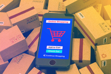mobile phone runs an online shopping app on packing cardboard boxes. business concept about transportation, global shipping, international freight, overseas trade, regional, services remotely.