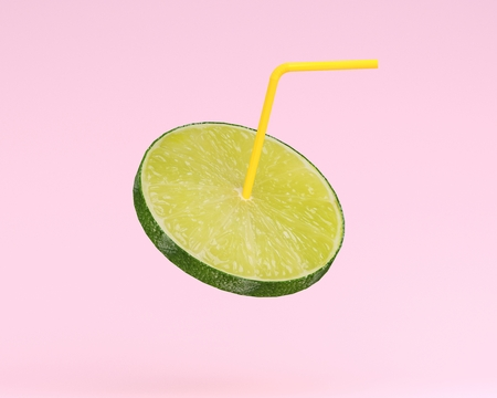 Lemon juice, Lime slice with Straw on pastel pink background. minimal fruit concept. Idea creative foods and drinks that are typically enjoyed at summer weather and summer festivals around the world