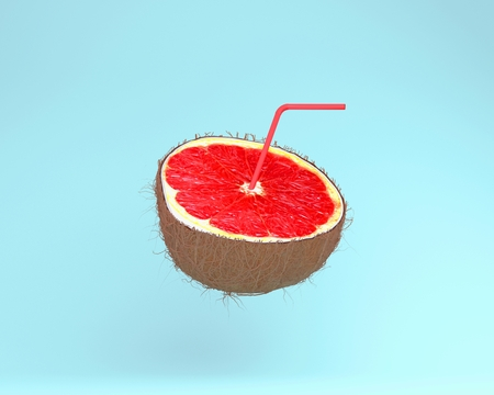 Grapefruit slice, juice with Straws in coconut on pastel blue background. minimal fruit concept. Idea creative foods and drinks that are typically enjoyed at summer times festivals around the world