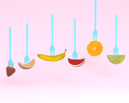 Creative layout made of fruits on the collection of forks on pastel pink background. minimal idea summer tropical fruits, diet healthy eating concept Reklamní fotografie