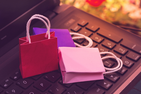 Business concept online shopping, paper shopping bags on notebook keyboard. Online shopping e-commerce or services on the internet is a transaction of buying or selling goods via electronic system Reklamní fotografie