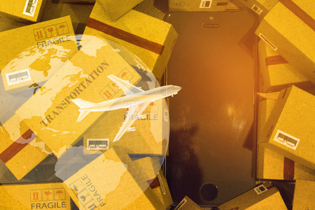 World map with mobile phone on pile of cardboard boxes. concept of International freight or shipping service for online shopping or e-commerce concept. freight forwarding business concept. Reklamní fotografie