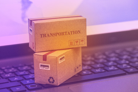 Concept of transportation and online shopping : Packaging cardboard boxes and notebook keyboard. International freight for online shopping, e-commerce that can be done easily using an online internet.