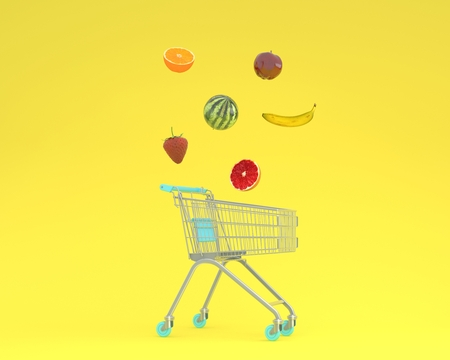 Creative idea layout shopping cart with fruits floating on yellow pastel background. minimal idea food and fruit concept.Ideas creatively to produce work within an advertising marketing communications Reklamní fotografie