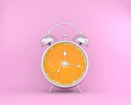 Tropical fruit concept made of orange slice alarm clock on pink pastel background. minimal idea business concept.
