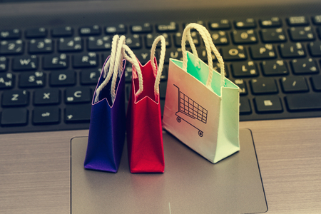 Online shopping concept, Three colorful paper shopping bags on notebook keyboard. E-commerce is the purchase of products and services on the internet can purchase goods or services foreign country. Reklamní fotografie