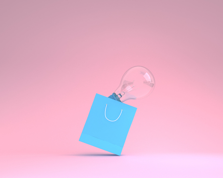 Blue paper shopping bags with incandescent light bulbs on pink color background. minimal business ideas. concept of retail consumers and shoppers looking for bargains and during the promotion Reklamní fotografie