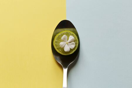 Creativity of flower with lemon slices and spoon on pastel pink and blue background. minimal idea food and fruit concept. top view
