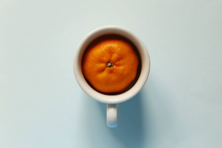 Creativity of orange with cup on pastel blue background.  minimal idea food and fruit concept.