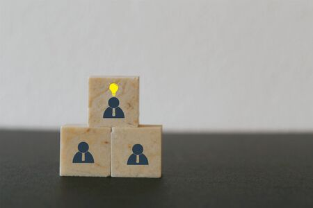 Concept creative idea, leader with idea and innovation. Marble block stacking with human symbol and light bulb icon
