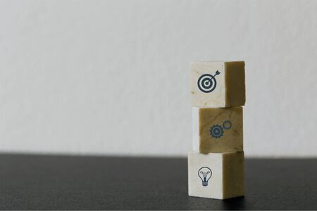 Arranging Marble cube block stacking with icon business strategy and action plan on wood background. Minimal concept