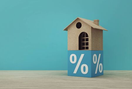 Creative idea of house model paper and percentage blue block on wooden table. Property investment real estate and house mortgage financial concept. 写真素材