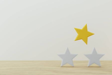 Outstanding yellow star shape on wooden table and white background. The best excellent business services rating for satisfaction.