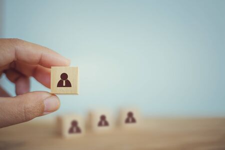 Recruitment business concept : Hand chooses wooden cube blocks are different with human icons. Human resource management, prominent crowds.