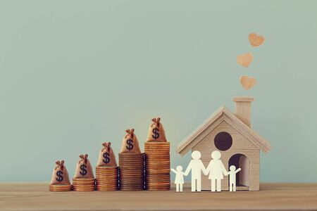 Mini house and heart, family members, US money bags on rows of rising coins on table. Family tax benefit, residential property tax concept: depicts home equity loan, real estate business investment. Standard-Bild