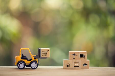 Logistic network distribution and cargo freight concept: Mini fork-lift truck moves a pallet with wooden block with icon. depicts delivering goods or products around globe in e-Commerce. Imagens