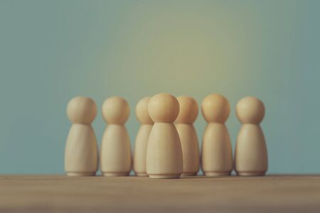 Successful business team leader concept: Wooden figures of man and people standing out from the crowd. depicts ability of individual to influence and lead followers or other members of organization.