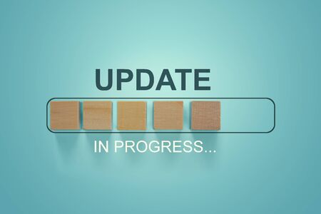 Wooden blocks with the word UPDATE  in loading bar progress.