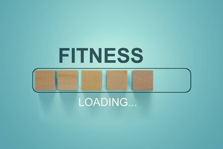 Wooden blocks with the word FITNESS in the loading bar progress concept. Stock Photo