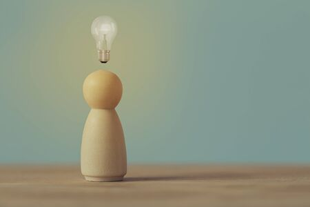 Creative idea and innovation. Human resource and talent management concept: Wood figures of people stand with light bulb glow. Depicts natural abilities to show specialized skills they possess person.