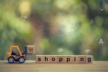 Logistic, supply / Online shopping concept: Fork-lift truck moves wood block and words shopping with icon customer network connection. International freight or shipping service for online shopping.