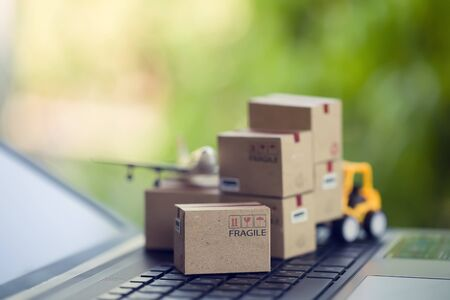Logistic and cargo freight concept: Fork-lift a truck moves a paper box on notebook keyboard in the natural green background. depicts International freight or shipping service for online shopping.