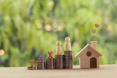 Small wooden house and heart, family members, words tax, on rows of rising coins on table. Family tax benefit, residential property tax concept: depicts home equity loan, real estate business investme