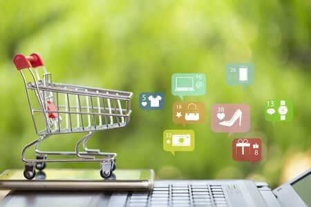 Online marketing and payment concept: Shopping cart with smartphone on laptop computer and icon online shopping and social media networking.