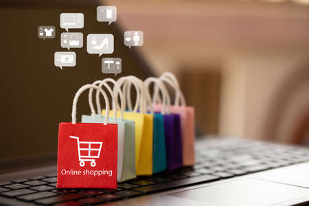 Online marketing and E-commerce concept: Paper shopping bags on notebook keyboard. Purchase of products and services on the internet can purchase goods convenient and safe 版權商用圖片