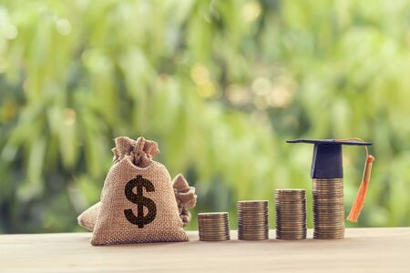 Black graduation cap, Hat and US dollar bag on rows of rising coins, on a table. Education funding, financial concept. Depicts savings for child knowledge for future studies