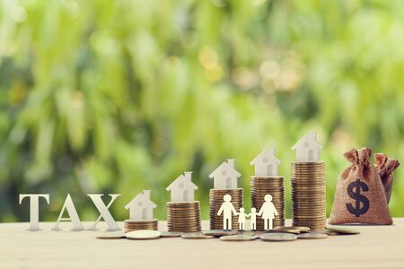 Family members, house, dollar money bags on rows of rising coins. Concept family tax benefit, residential property or estate taxt depicts home equity loan, reverse mortgage Stock Photo