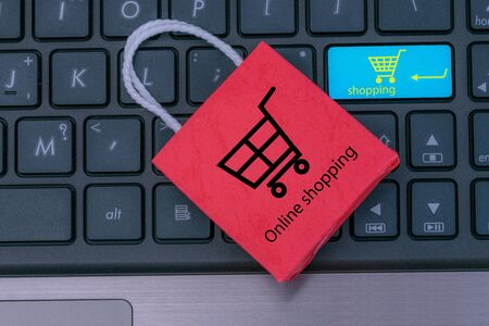 Small red paper shopping bags on laptop keyboard.Wait for the customer to click the button. for shopping at home or office which customers can purchase items or services or goods remotely.